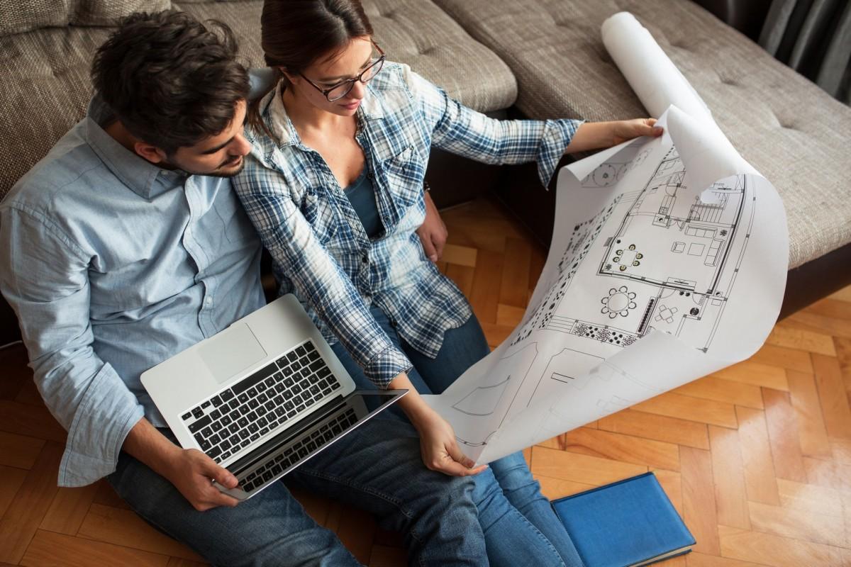 Un jeune couple examine les plans de son futur logement