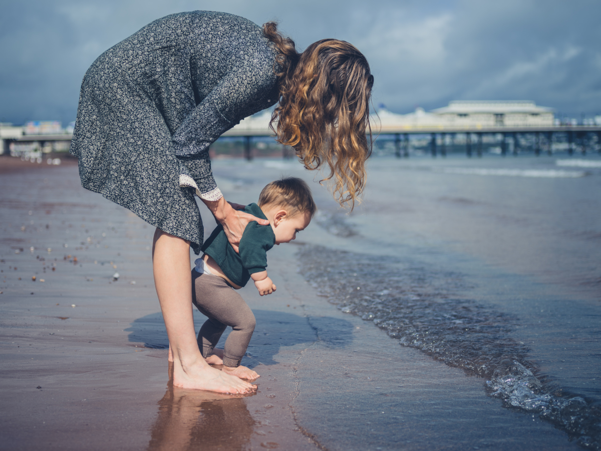 Une mère aide son bébé à marcher sur la plage