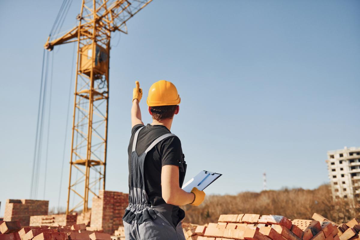 Promoteurs immobiliers à Rennes – Ouvrier constructeur sur un chantier immobilier fait un signe de la main à une grue.