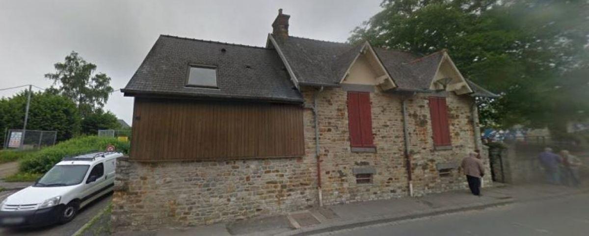 Une petite maison avec une façade en pierres au bord de la D 231, à Montgermont