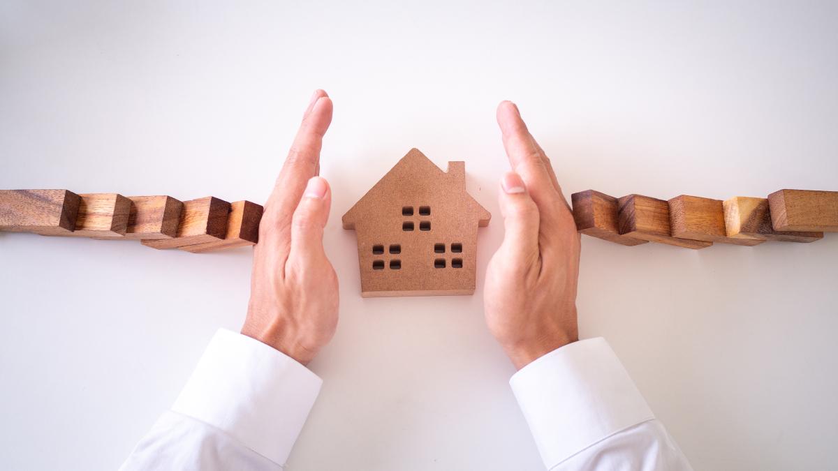 louer appartement rennes - Mains sécurisant une maison en bois et symbolisant les garanties constructeur