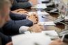 Loi Climat– Hommes en costume qui croisent les mains sur une bureau avec micro