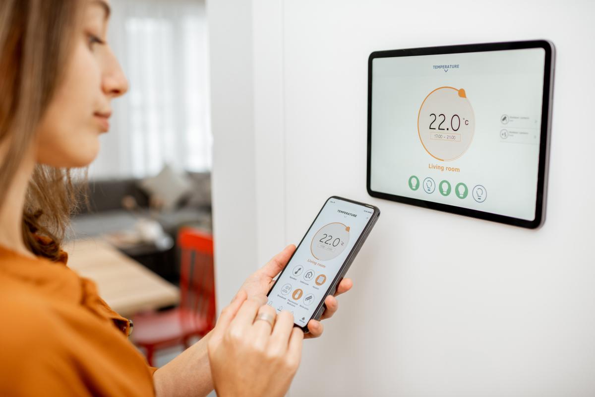 Appartement rez-de-jardin à Rennes – Femme qui utilise un système domotique pour le chauffage de son appartement