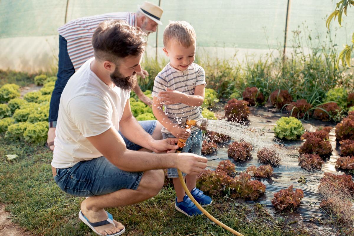 Appartement rez-de-jardin à Rennes – Famille qui arrose les plantes dans un jardin