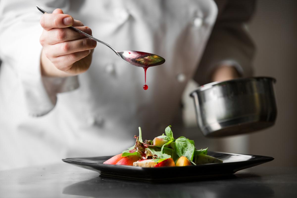 Legendre Immobilier – Cuisinier verse de la sauce sur une assiette