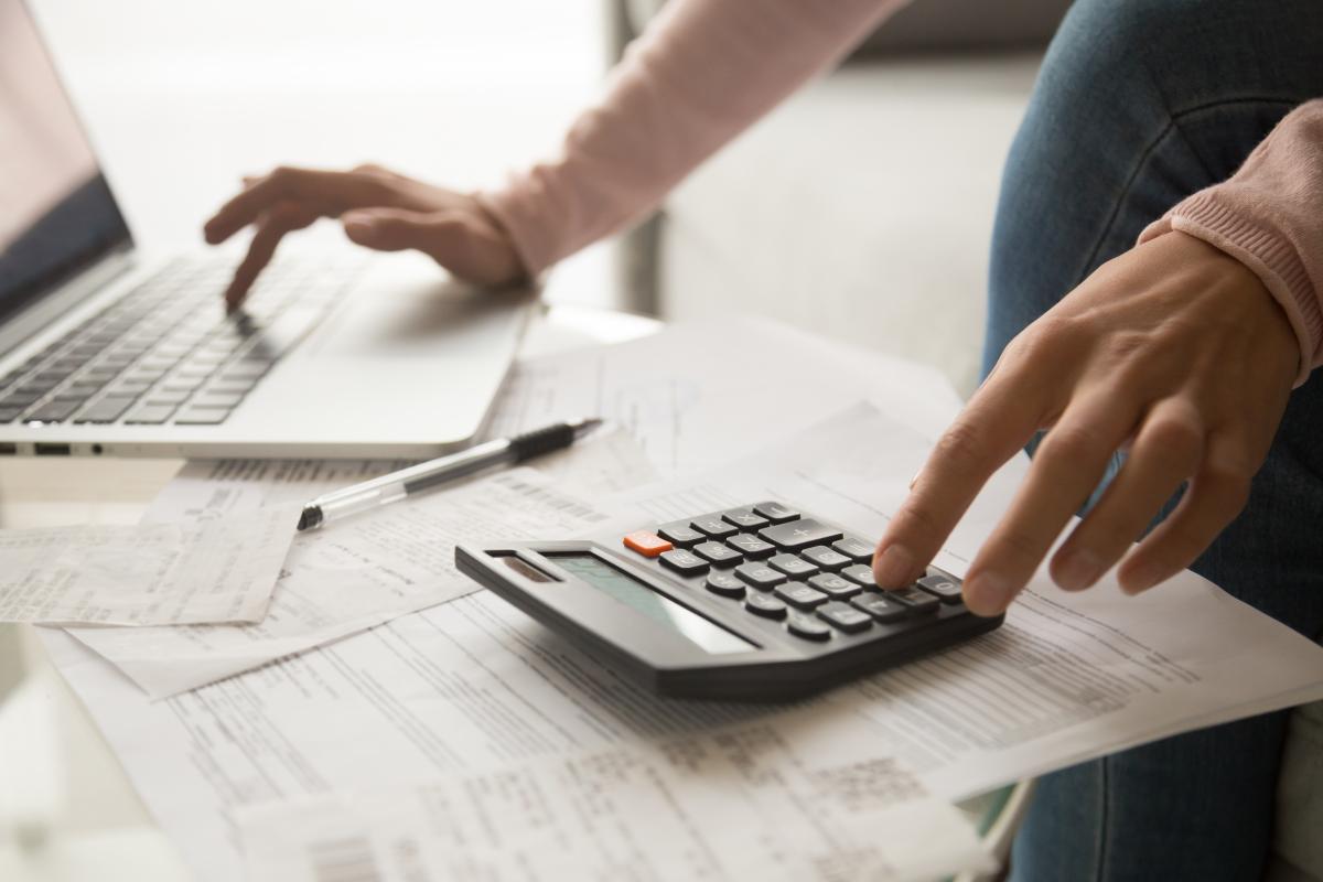 Programme neuf Rennes - Une femme faisant sa comptabilité mensuelle avec une calculatrice et un ordinateur portable