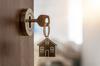 Clé sur une porte ouverte avec porte-clé en forme de maison